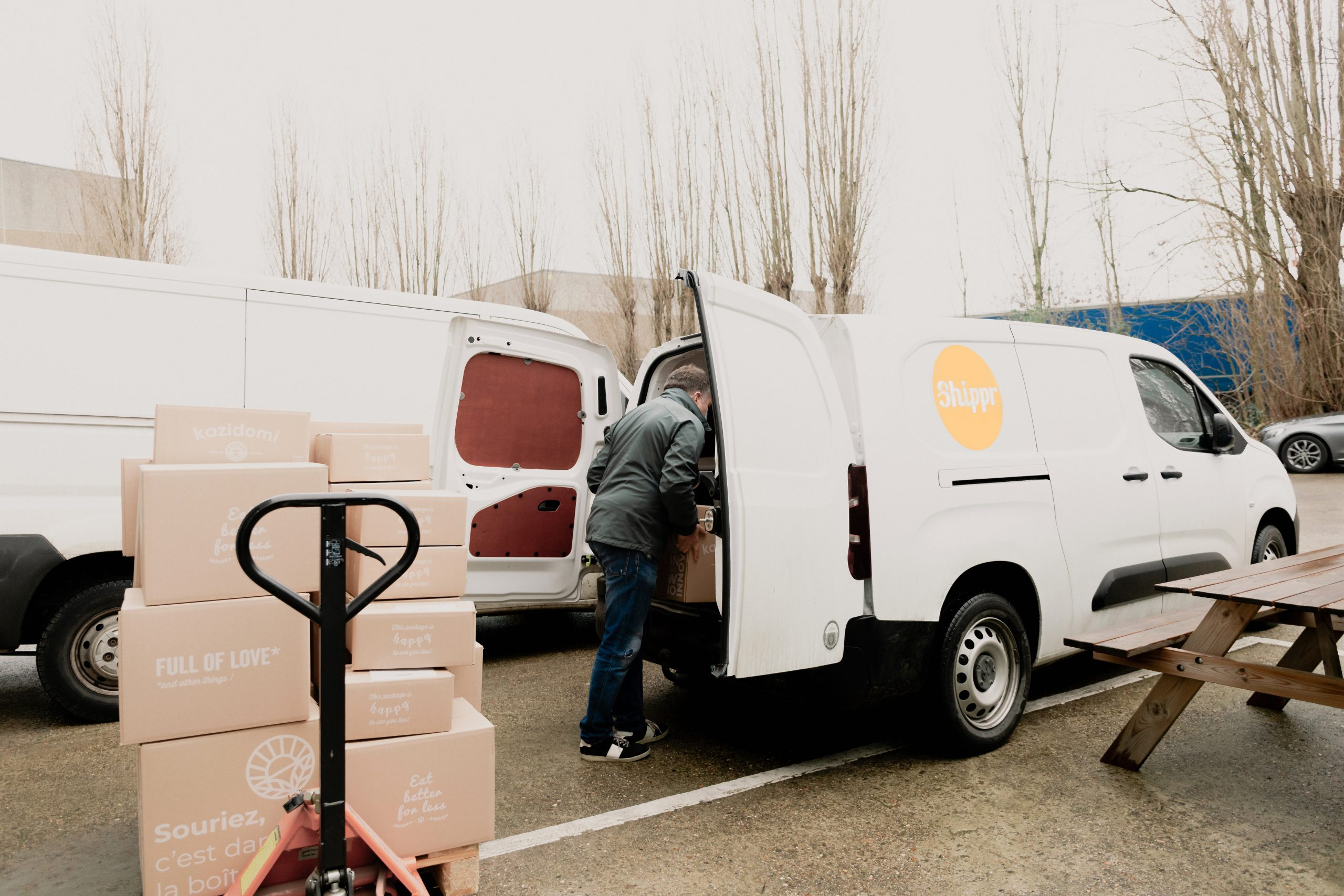 Livreur Shippr mettant des caisses en carton dans sa camionnette blanche