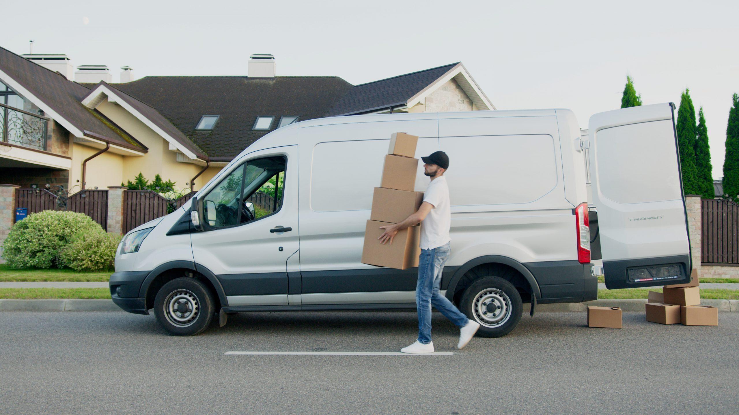 Livreur en camionnette qui porte des caisses en carton dans une rue résidentielle.