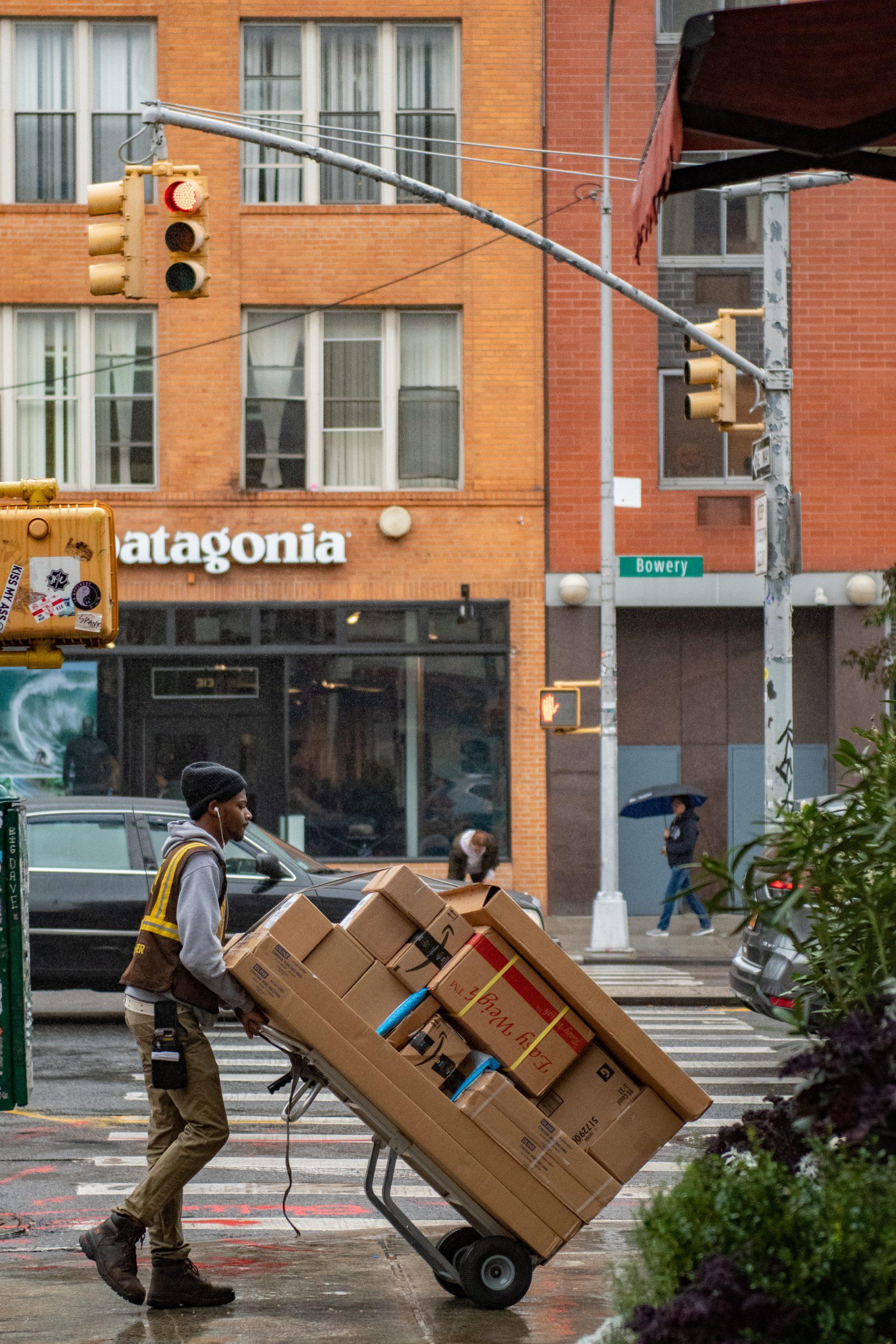 Livreur en rue qui transporte des caisses sur un diable