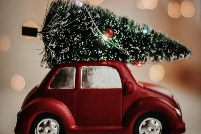 Voiture rouge transportant un sapin de Noël sur le toit